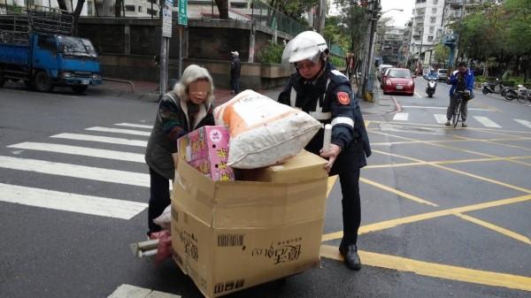 三重警分局永福派出所巡佐曾世宗,幫許老太太推著載滿回收物的推車。(記者謝君臨翻攝)