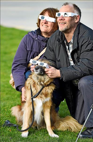 英國利物浦水岸碼頭邊,一對情侶和他們的愛犬戴著防護鏡觀看日偏蝕。(法新社)