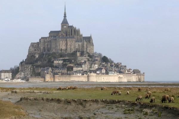「聖米歇爾山」與海岸距離約1公里,平常周圍被大片淤沙包圍。(路透)