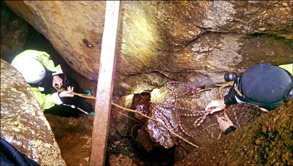 消防與警察先用繩子綑綁自己,再入洞救援。(記者吳政峰翻攝)