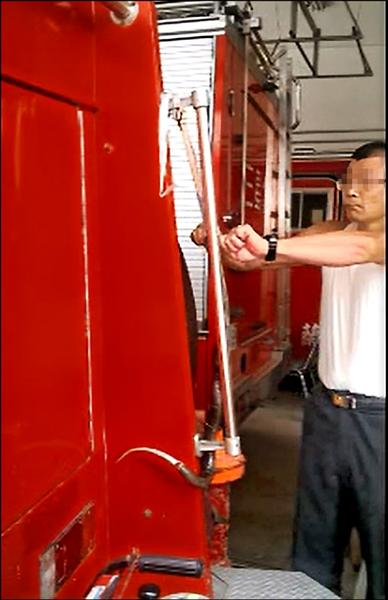 賴姓消防員在消防車上宰殺眼鏡蛇。(記者朱則瑋翻攝)