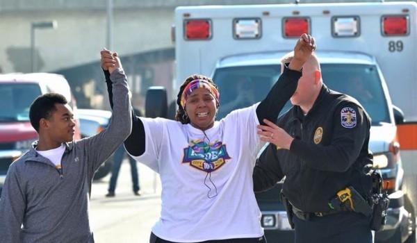 婦人在警察和兒子的幫助攙扶下,順利抵達終點。(圖擷取自Mayor Greg Fischer臉書)