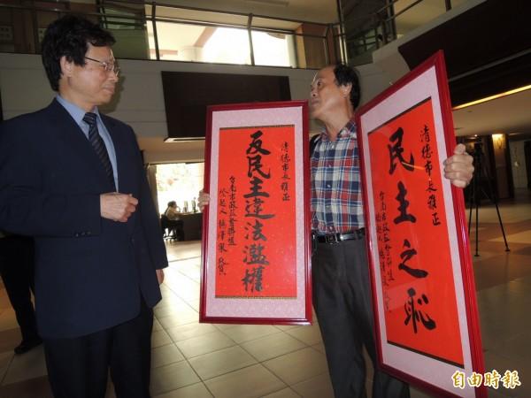 楊澤泉(右)拿著匾額赴市府要送給賴清德,由市府顧問黃先柱(左)接下匾額。(記者洪瑞琴攝)