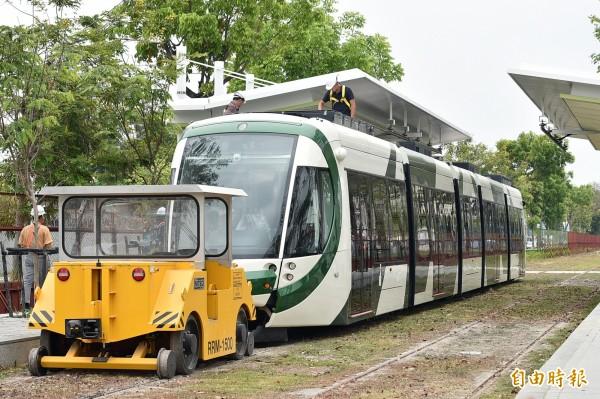 高雄環狀輕軌捷運列車,25日首次在上班時間進行動態測試,路上人車不少,引起許多民眾側目。(記者張忠義攝)