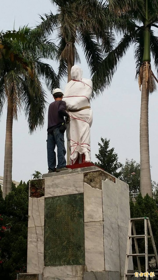 台南市14所國中小校園內的蔣中正銅像被拆除,圖為當時工作人員將銅像包裹,進行拆除作業。(資料照,記者黃文鍠攝)