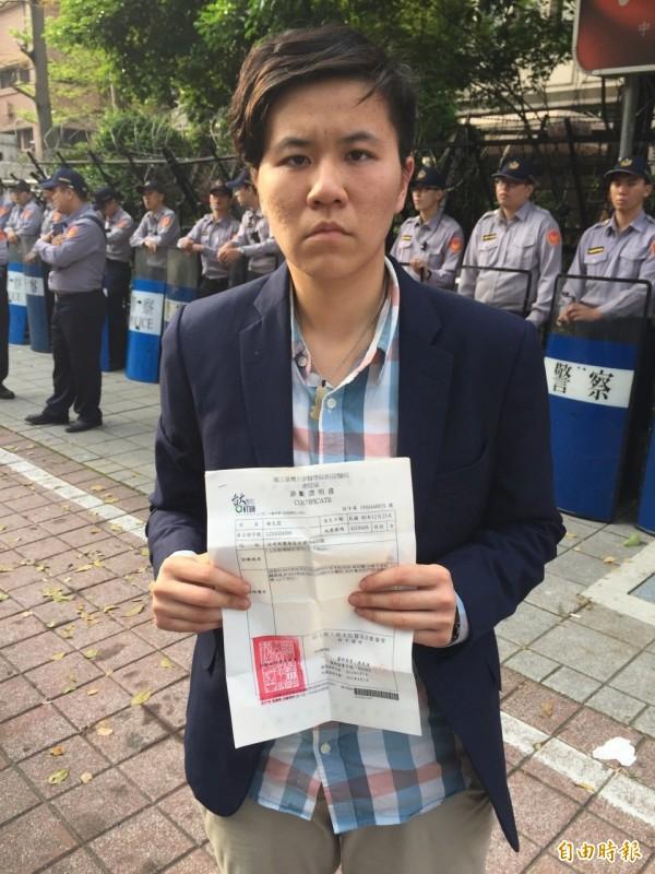 「民主鬥陣」的謝邑霆拿出驗傷單,指控執法單位濫用暴力,踹傷她的左肋骨。(記者曾健銘攝)