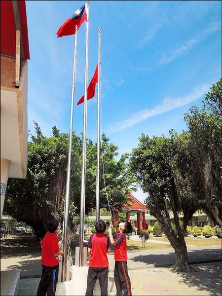 雲林縣水燦林國小前天搶先升起紅色空污旗,提醒學童保護自己健康。(記者林國賢攝)