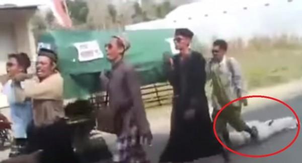 印尼一列送葬隊伍在抬棺送行時,屍體居然從棺木中掉了出來。(圖取自YouTube影片)