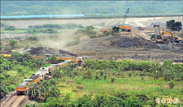 桃園、板新約三百萬人口的備援水庫「中庄調整池」預定地,數十輛砂石車排隊倒廢土。(記者張嘉明攝)