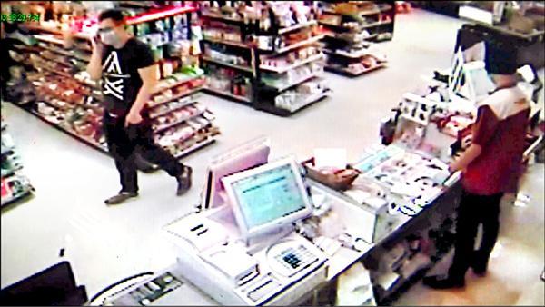 假「盧冠霖」佯裝店員站在櫃台操作,另一位戴著口罩歹徒則走來走去把風。(記者蔡宗勳翻攝)