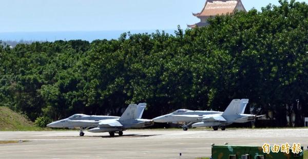 2架美軍F-18戰機一前一後滑行至跑道頭,先後起飛離開台南空軍基地。(記者黃志源攝)