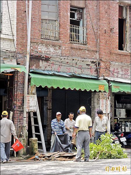 鹽埕九十年紅磚老屋「慶雲藥行」,在市府文化局緊急列為「暫定古蹟」,暫時阻止老屋被拆,工人在清理現場後離去。(記者黃良傑攝)
