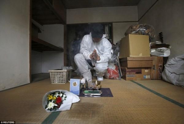 日本高齡化社會帶來許多問題,獨居老人在家中過世的情況遽增,因此有業者專門處理往生者的住處。圖為業者在清掃後,於遺體位置點香祭拜死者。(圖擷取自《每日郵報》)