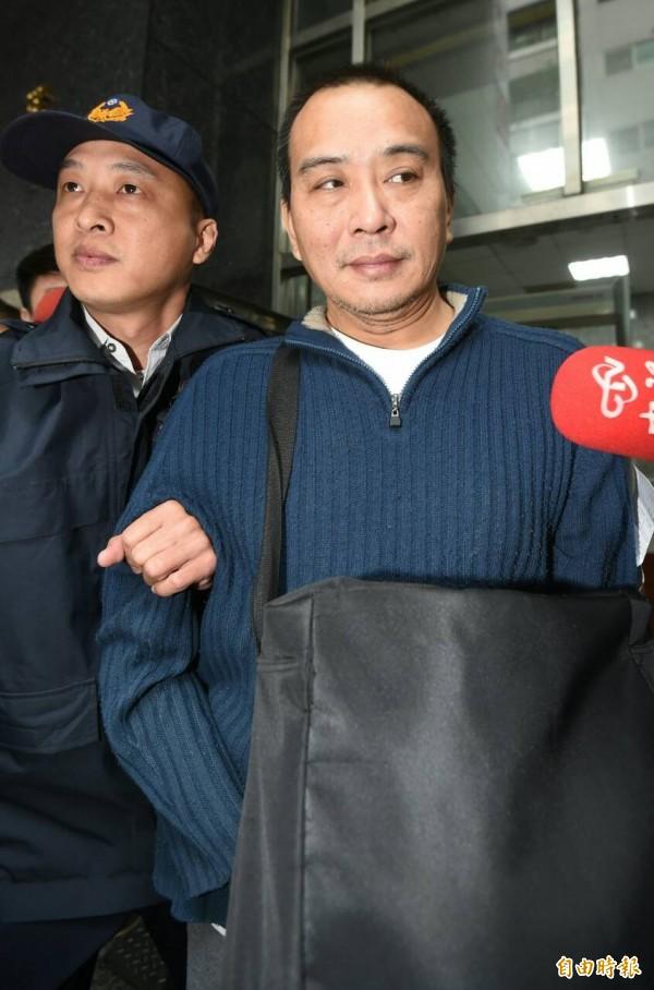 導演張作驥上午前往北檢報到,隨即搭上囚車發監入獄。(記者劉信德攝)