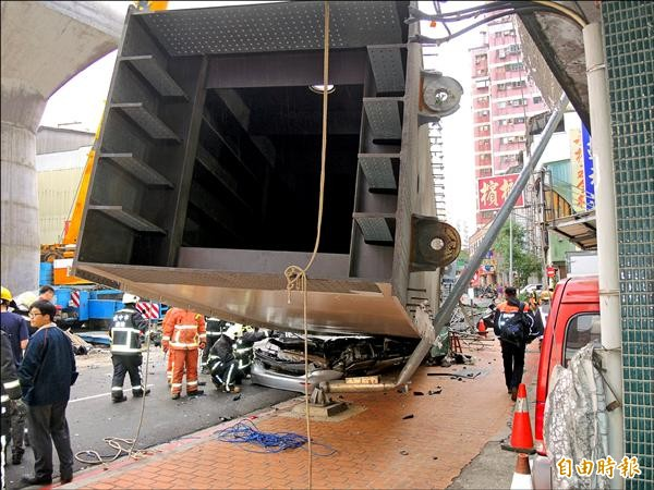 台中捷運吊掛209公噸鋼樑作業時墜落,掉落在北屯路上,當場把一輛銀色自小客車壓成鐵餅。(記者林良昇攝)