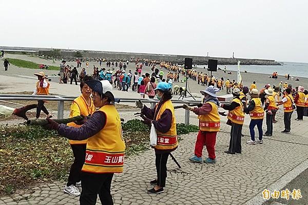 志工們連接成螞蟻雄兵長龍,接力清走沙灘的垃圾。(記者蔡文居攝)
