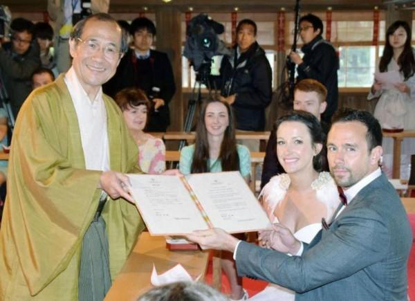 京都市長門川大作(左)親自頒發編號第1號結婚證書給來自英國的愛侶。(圖擷取自《日本時報》)