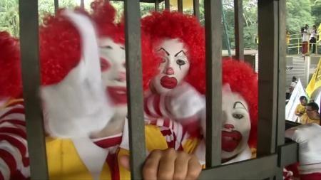 巴西麥當勞員工扮成「麥當勞叔叔」,卻身處大牢,表達對公司的不滿。(路透)