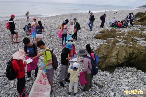 許多家長攜家帶眷參加淨灘活動,讓孩子提早認識環境生態的重要。(記者王峻祺攝)