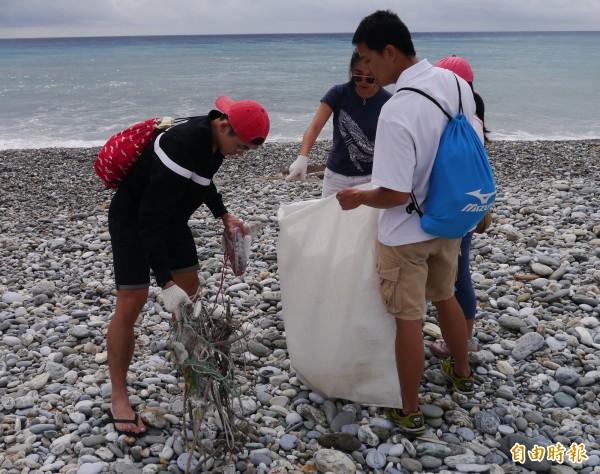 青年志工努力撿拾海邊垃圾,守護海洋環境生態。(記者王峻祺攝)