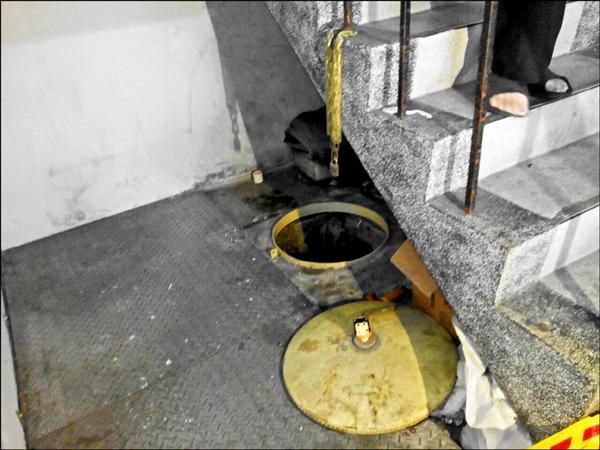 新北市板橋一棟公寓地下儲水槽內驚見一具男性裸屍,害住戶喝了12天屍水。由於遺體腫脹一度無法拉出,里長協助雇工抽水、鑿破槽壁排水,折騰5小時後總算拉出。(記者吳仁捷翻攝)