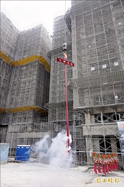 北大安置住宅工程單位,昨天將安置宅屋頂最高的一根中脊樑以起重機吊掛上位,祈求工程圓滿。(記者張安蕎攝)