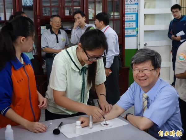 北港國中學生為教長吳思華手部彩繪,展示自己所學。(記者林曉雲攝)