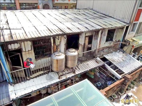 三棟緊鄰的平房建築,二樓加蓋鐵皮屋材質,被大火燒成塌陷。(記者張勳騰攝)