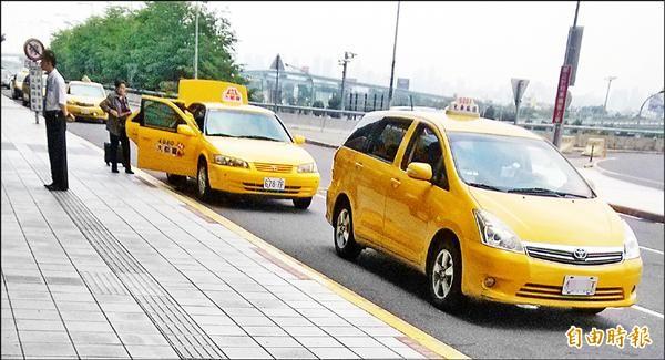 計程車(右)違停2樓轉運層,在車內就不停招手攬客。(記者俞泊霖攝)