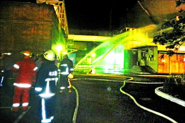 火警後廠內人員消防灑水。(記者蔡宗憲翻攝)