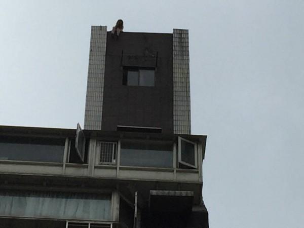 1名年齡不詳的年輕女性,9時53分坐在台北市錦州街8號的大樓屋頂水塔上,疑似有跳樓經生念頭。(記者劉慶侯翻攝)