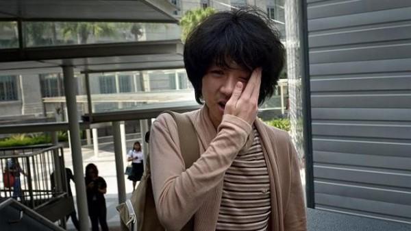余澎杉今步入法院時,突遭一名陌生男子襲擊,被打中左臉,甚至挑釁嗆說:「來告我吧!」(圖取自海峽時報)