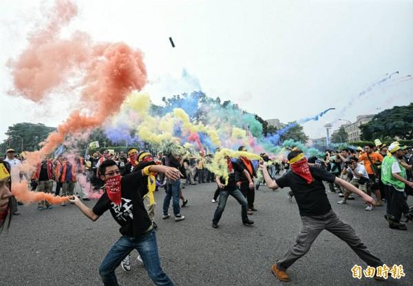 五一勞工大遊行參加遊行的勞工向總統府丟擲煙霧彈。(記者王敏為攝)