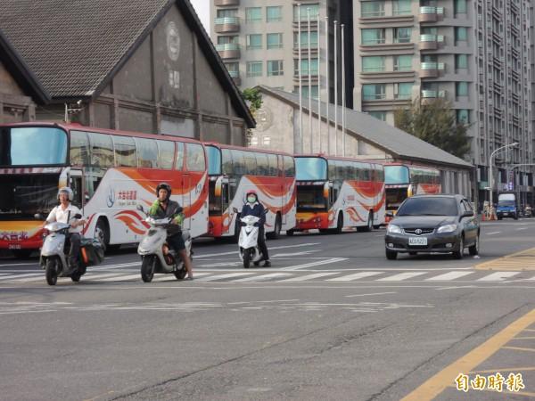中客遊覽車因中山大學管制,百輛遊覽車外溢轉臨海新路違停,迫使機車騎進快車道惹議。(記者黃良傑攝)