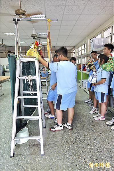 鋁梯、曬衣杆、塑膠矮凳與長條木板,鹿港國中完成創意布袋戲台。(記者劉曉欣攝)