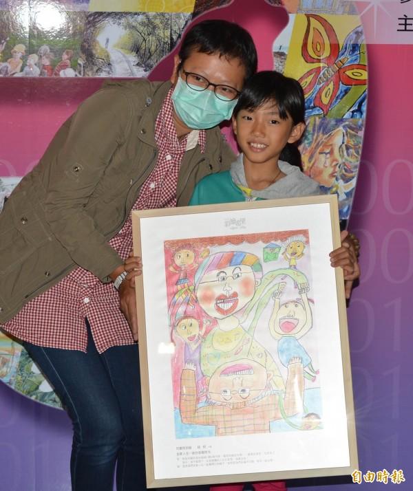 小女生「紐紐」把畫作「全家人在一起的甜蜜時光」送給罹癌的母親李亦蕿,還獻上一吻,祝她母親節快樂。(記者湯世名攝)