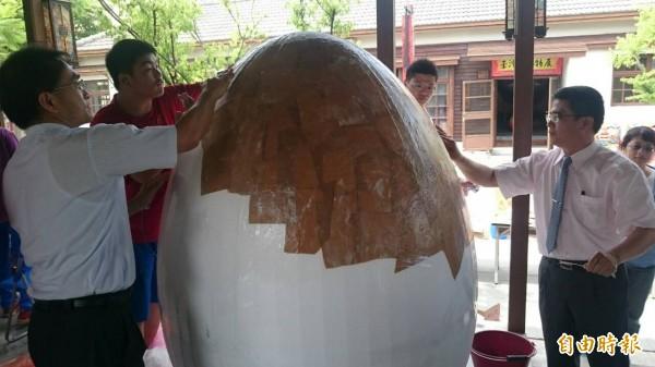 鹿港鎮長黃振彥(右)等人以保麗龍、牛皮紙製做高達2公尺高的「巨蛋」,站在巨蛋旁明顯小了一號。(記者湯世名攝)