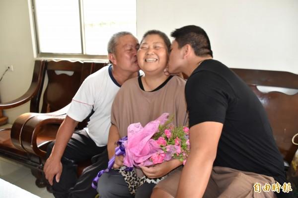 丈夫和兒子分坐兩旁親吻臉頰,讓黃素娥充滿對抗病魔的能量。(記者蘇福男攝)