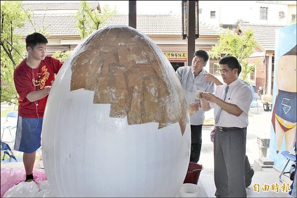 鹿港鎮長黃振彥(右)等人以保麗龍、牛皮紙製做高達兩公尺高的「巨蛋」,站在巨蛋旁明顯小了一號。(記者湯世名攝)
