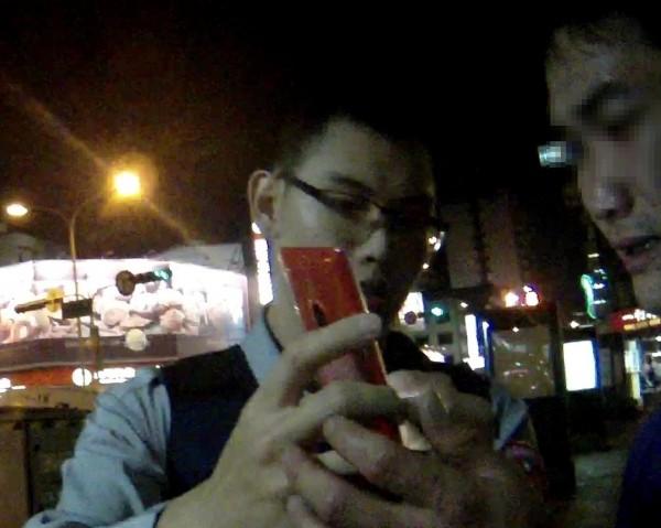 員警拿出智慧型手機,與鄭男(右)用打字溝通。(記者林良昇翻攝)