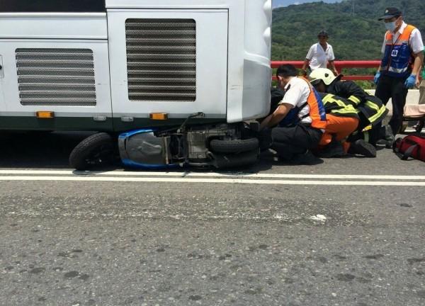台中市張姓少年今天中午在太平一江橋撞上公車,人車卡在車底,消防人員緊急到場救人。(記者陳建志翻攝)