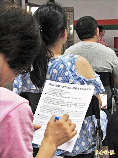 新北市議員陳儀君試辦「參與式預算」,昨天在達觀里活動中心舉行第一階段說明會,出席的民眾仔細的研讀說明資料。(記者何玉華攝)