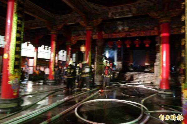 伸港福安宮深夜大火獲得控制之後,消防人員清理火場。(記者劉曉欣攝)