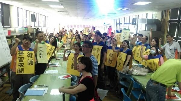 基隆市仁愛國小十八日早上教師晨會,多數教師舉牌表達「捍衛學子權益,反對出借教室」的立場。(圖為關心教育人士提供)