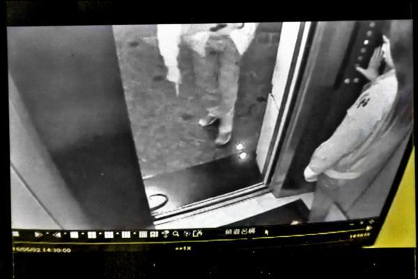 後方另一名準備進入電梯的男員工,被竄出的蛇嚇著,後退閃避,指著蛇大喊,電梯內女員工則不知所措。(圖由讀者提供)