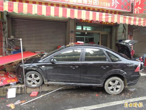 黑色自小客車衝進花生糖老店,造成店面毀損。(記者林孟婷攝)