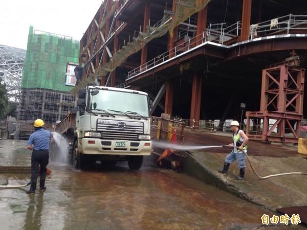 大巨蛋今上午9時復工,砂石車陸續進出。照片為砂石車離場前,工人針對輪胎做沖洗作業。(記者何世昌攝)