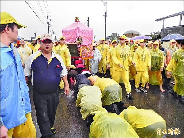 白沙屯媽祖鑾駕進入斗南鎮,信徒顧不得大雨爭相跪地鑽轎腳。(記者廖淑玲攝)