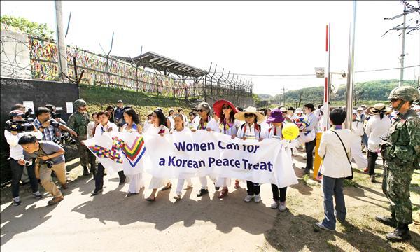 女權人士二十四日穿越南北韓邊界從北韓進入南韓。她們拉開布條,呼籲簽訂永久性的和平協議,取代停戰協定。(美聯社)