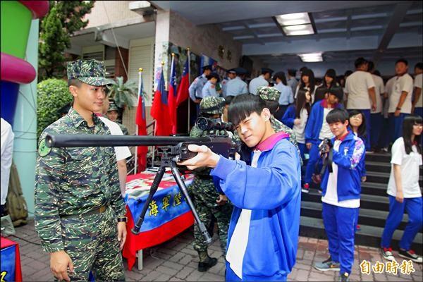 國軍昨到達德商工推廣國防教育,學生好奇拿起海軍陸戰隊的狙擊槍模擬射擊。(記者陳冠備攝)